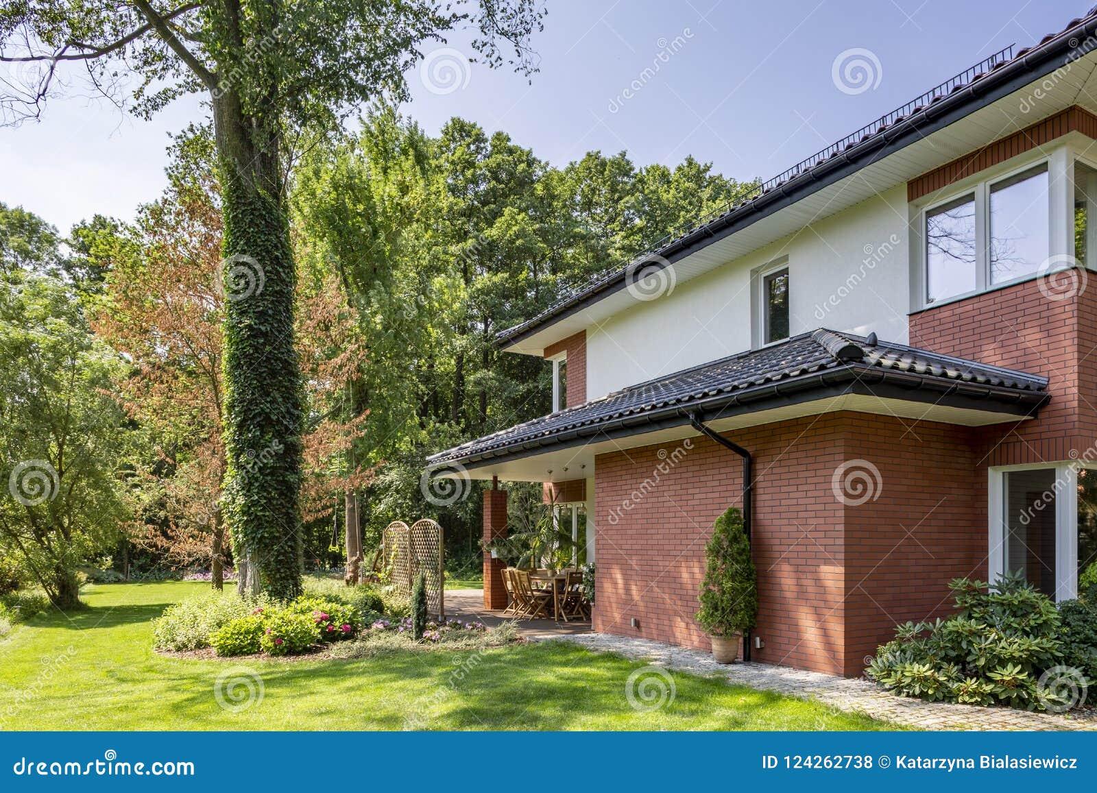Parede de tijolo vermelho da casa com telhado e janelas