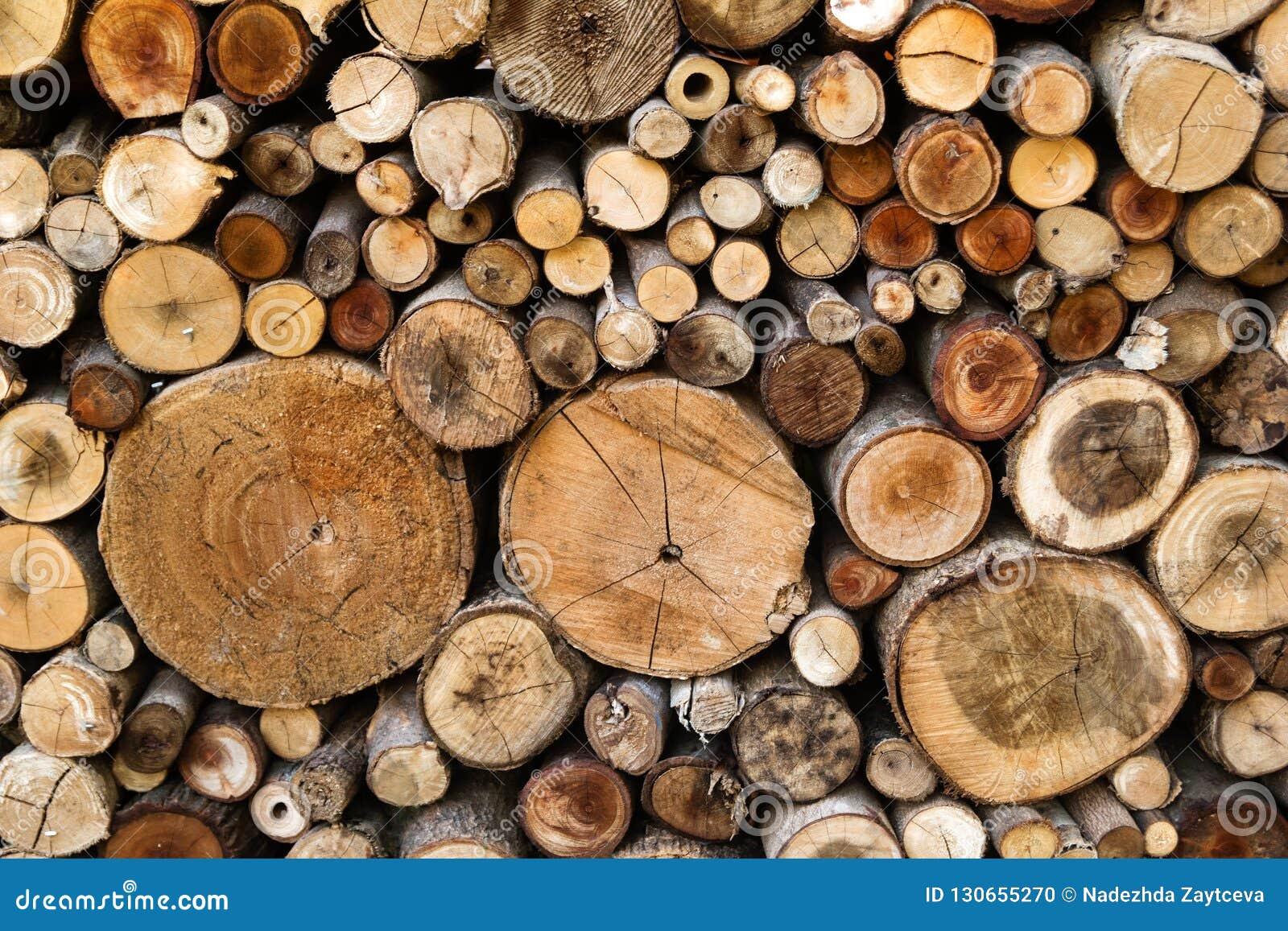 Parede dos logs desbastados secos da lenha empilhados acima sobre se em uma pilha Textura de madeira do Close-up