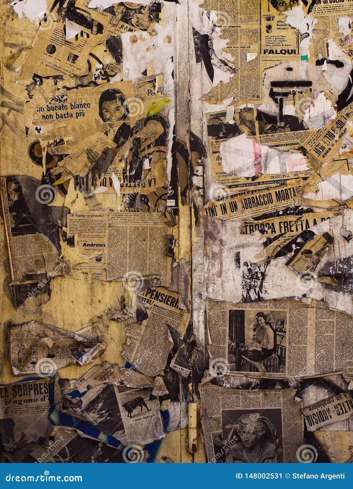 Parede forrada com os jornais rasgados e velhos