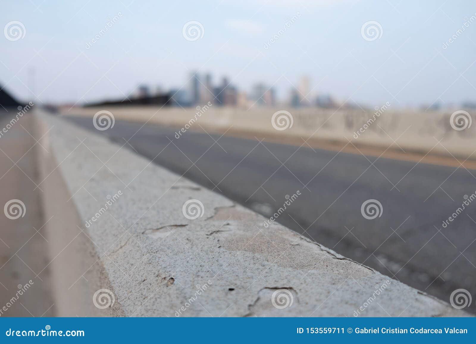 Parede lateral da estrada com a cidade borrada no fundo