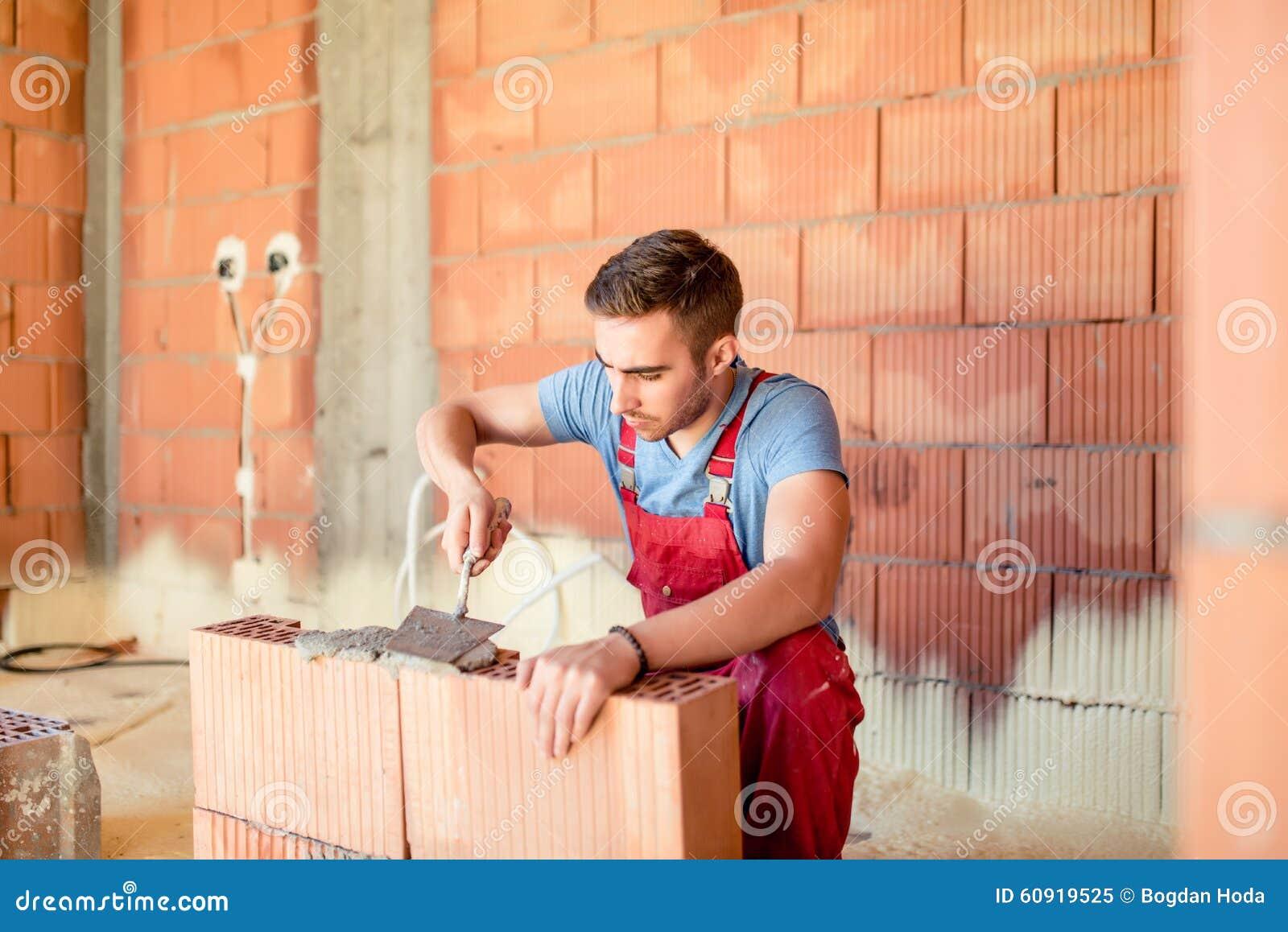 Paredes de tijolo da construção do trabalhador da construção do pedreiro, contratante que renova a casa Detalhes da indústria da