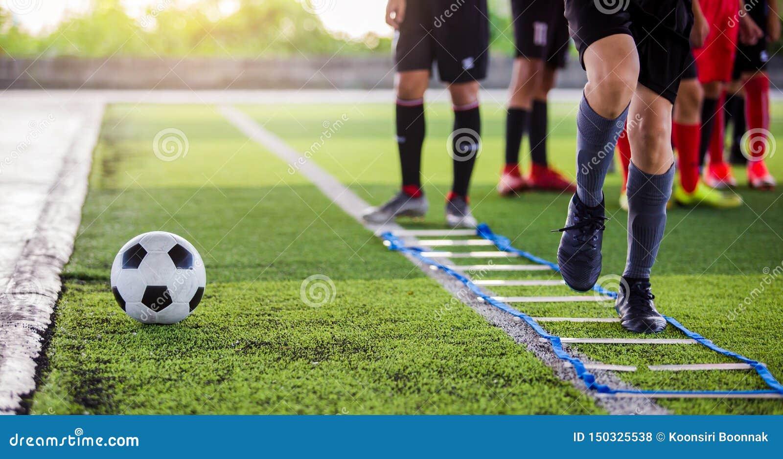 Pareggiare e salto del calciatore fra l indicatore per addestramento di calcio La scala perfora gli esercizi per la squadra di ca
