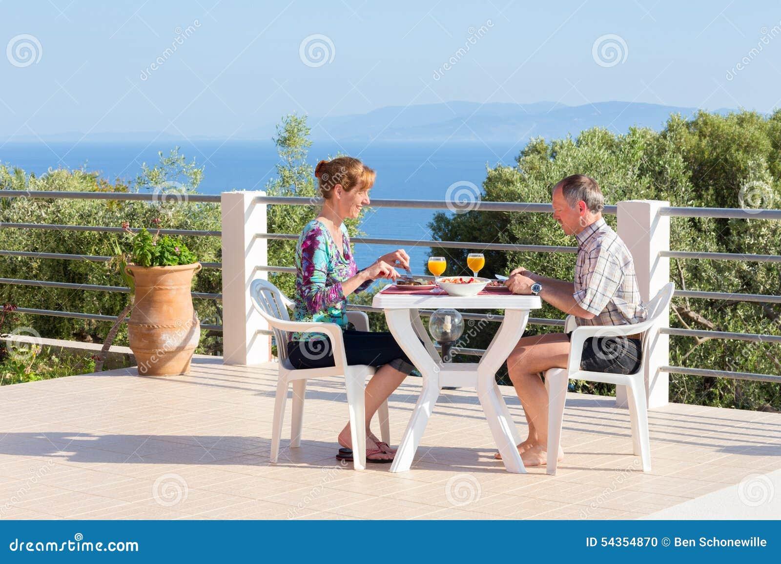 Pareja casada que come en la tabla en terraza cerca del mar