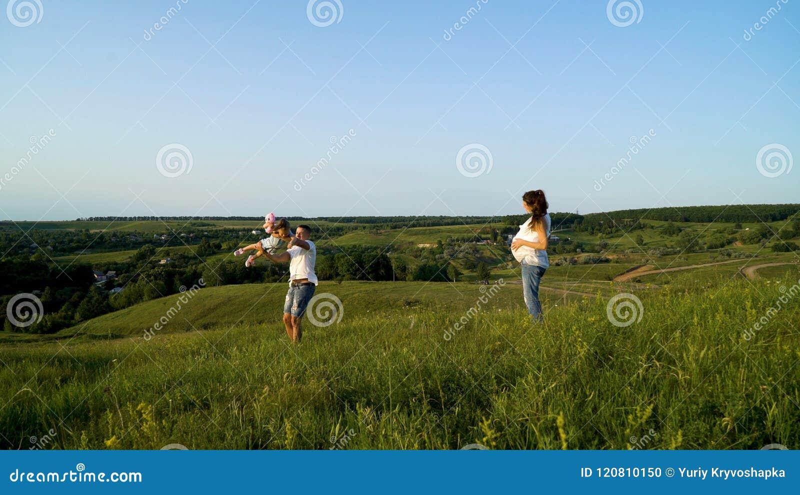 Pareja embarazada con la hija del niño que camina en los campos verdes que tienen tiempo libre
