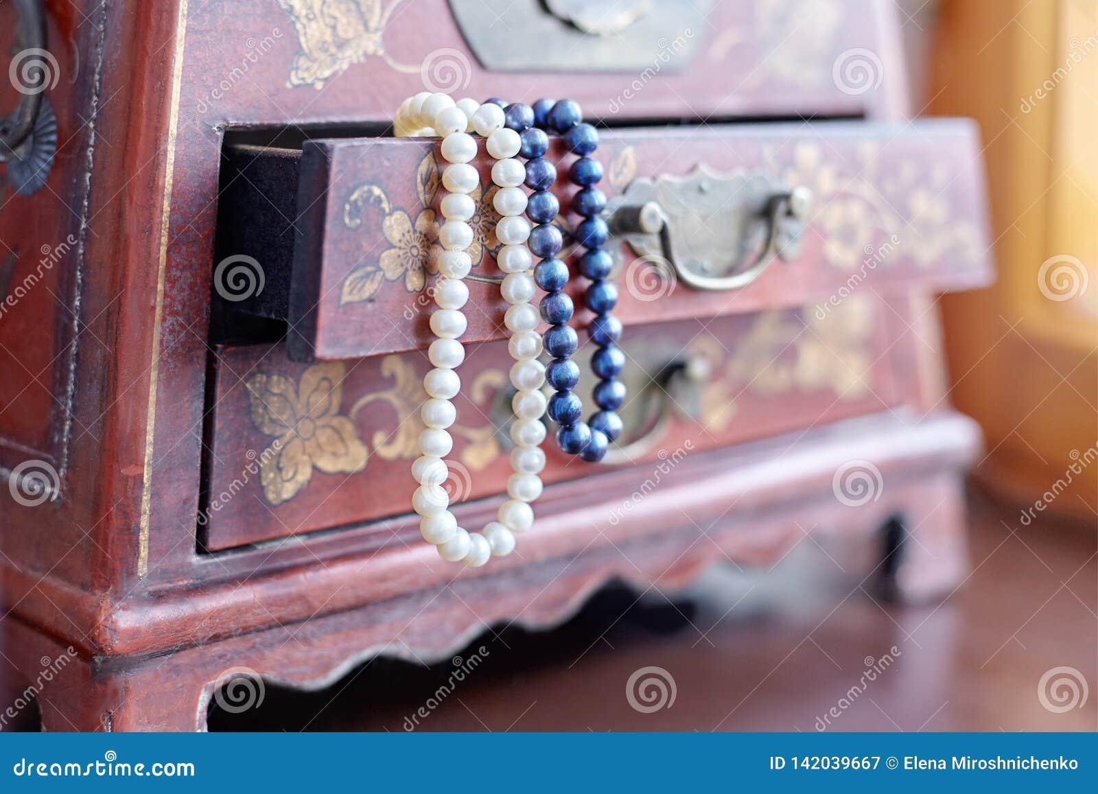 Parels in een Doos Twee halsbanden witte en lilac parels in geopend uitstekend geval met mooie ornamenten op houten oppervlakte