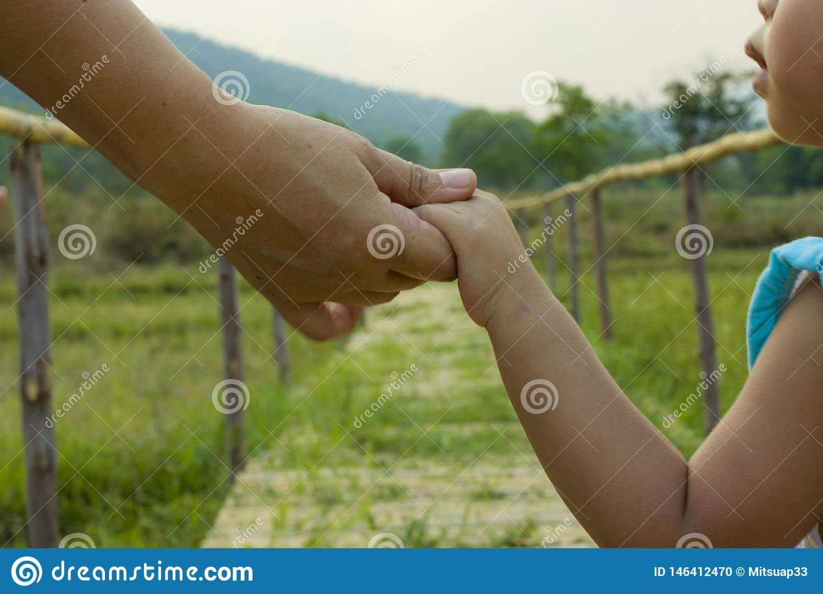Parent holds the hand of a little child green background, soft focus