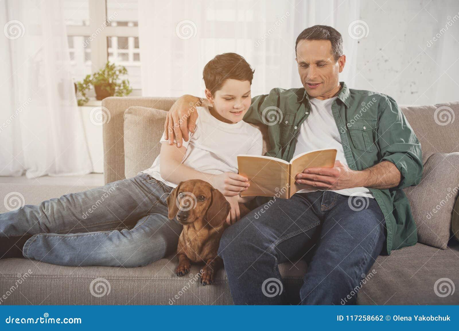 Parent joyeux et enfant détendant à la maison avec le chiot de teckel