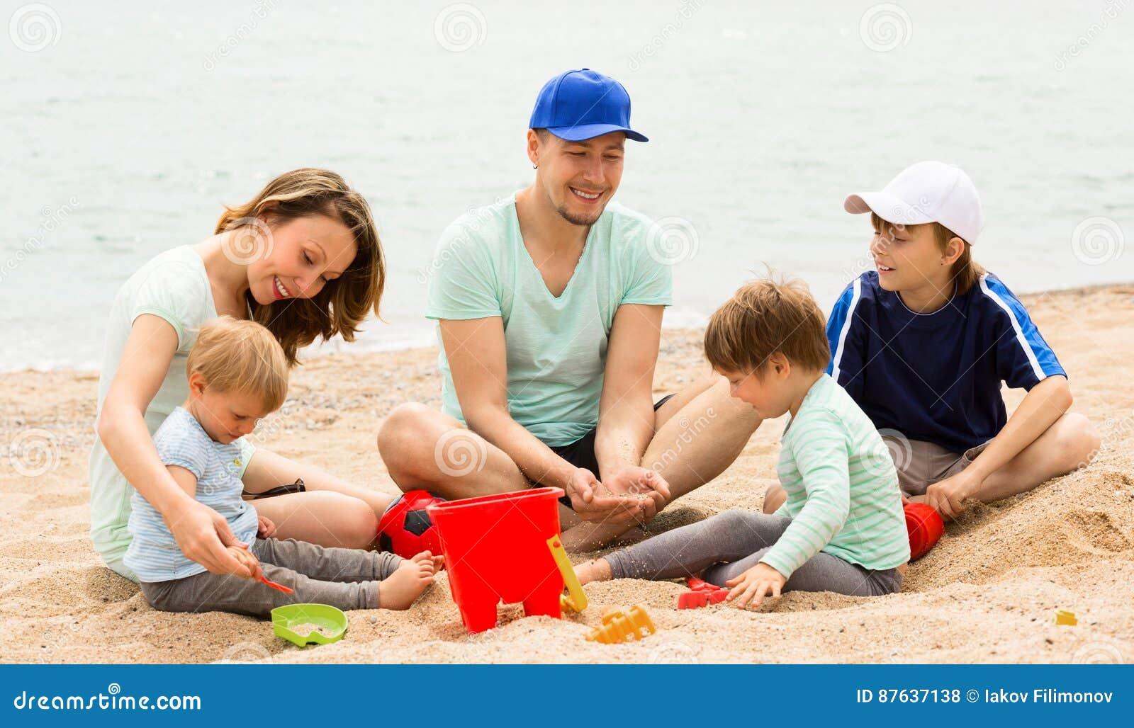Parents avec trois enfants sur la plage