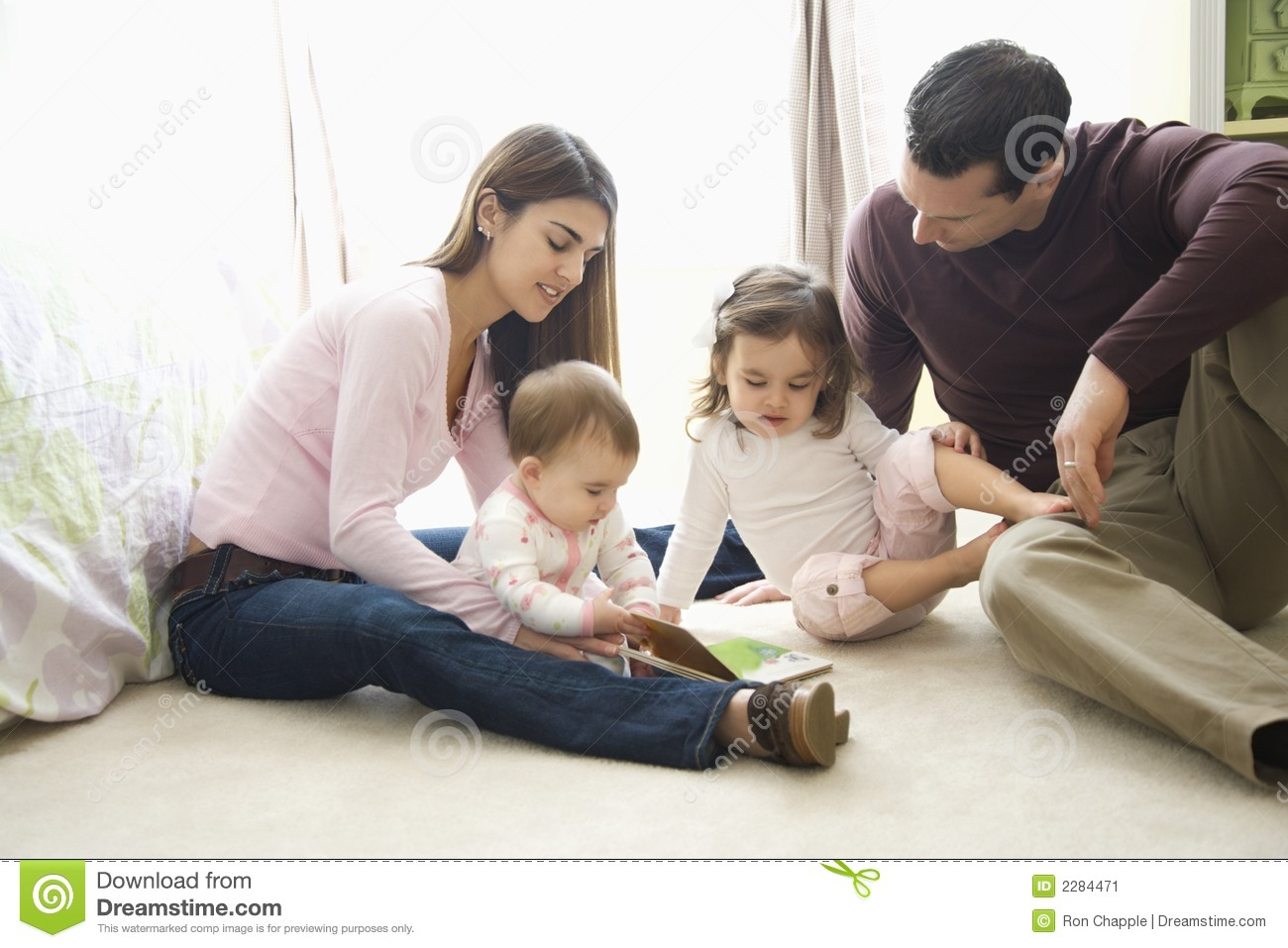 Caucasian female children with mother and father sitting on bedroom ...