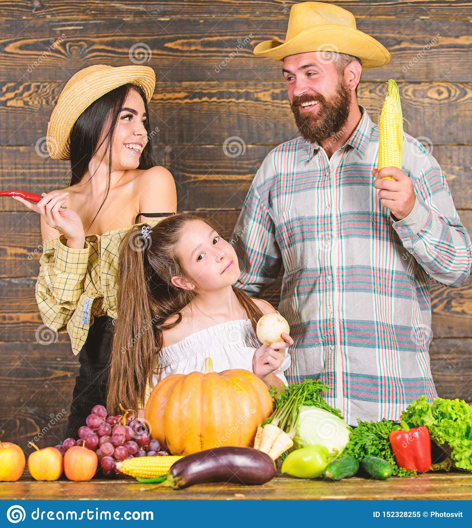 Parents and daughter celebrate autumn harvest festival. Family rustic style farmers at market with vegetables fruits and