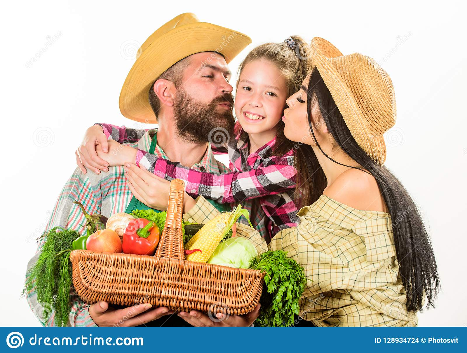 Parents and daughter farmers celebrate harvest holiday. Family farm concept. Family farmers hug hold basket fall harvest