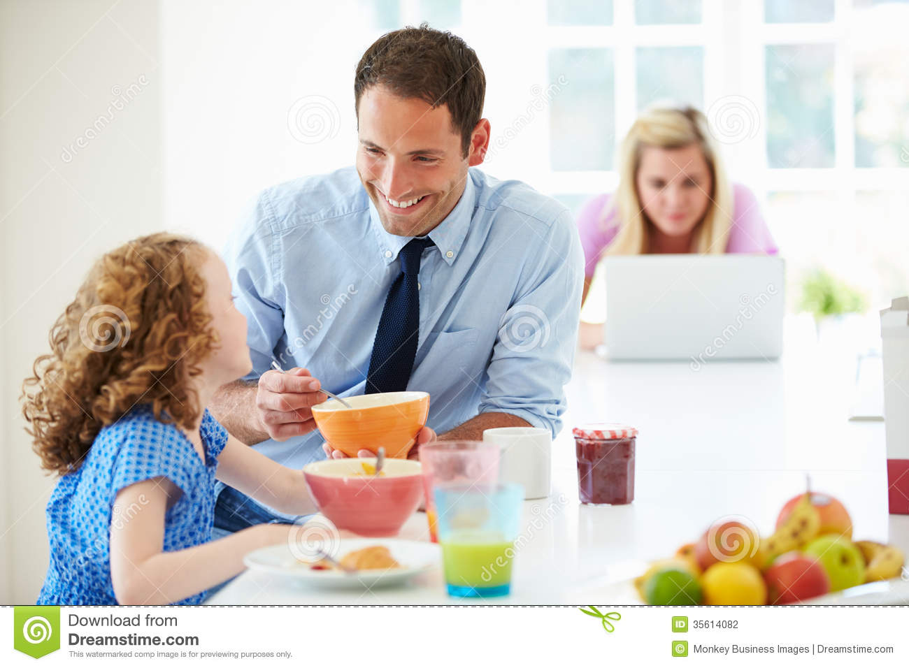 Parents And Daughter Having Breakfast In Kitchen Together ...