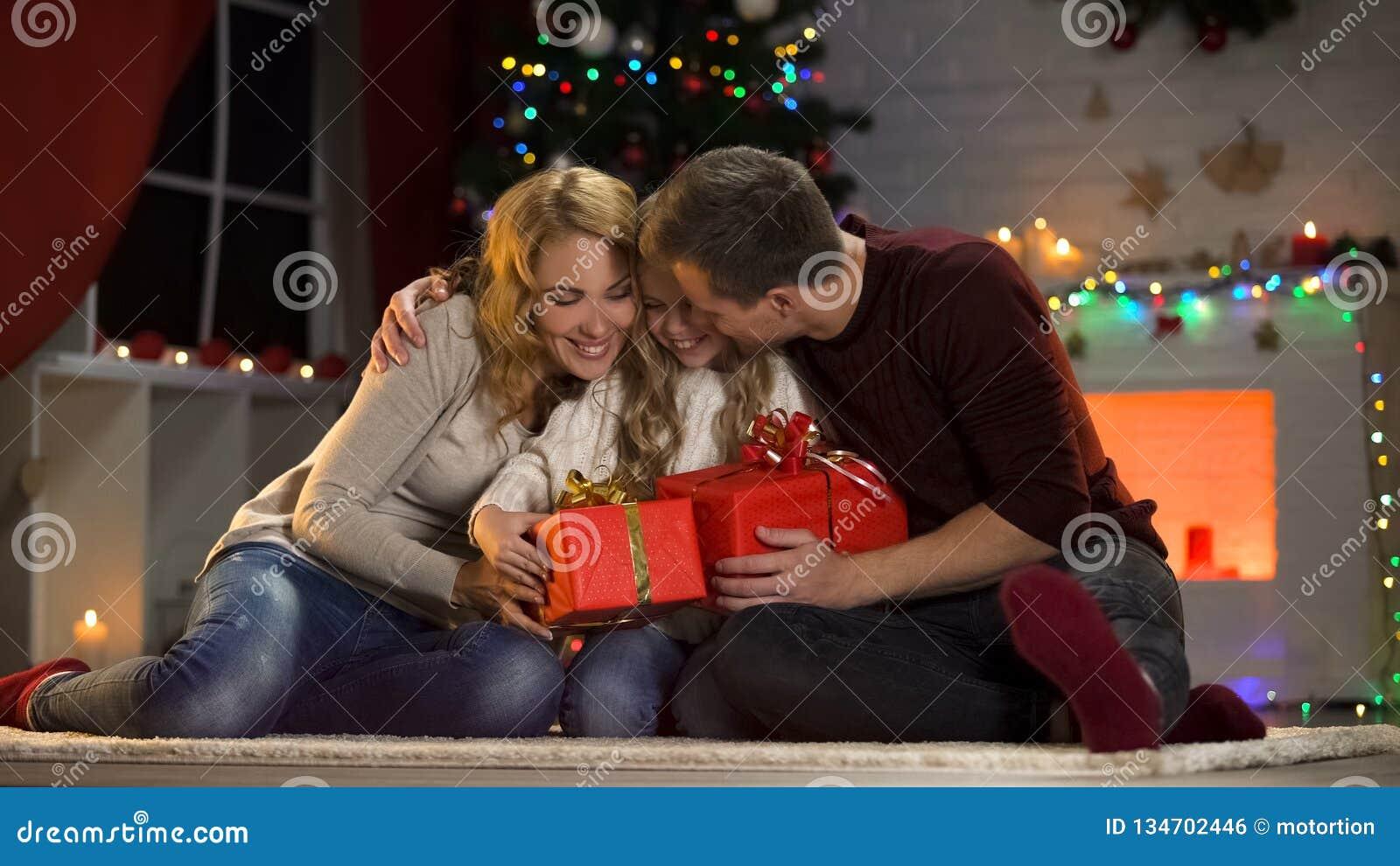 Parents de soin donnant à peu de fille enthousiaste des présents de Noël, tradition de famille