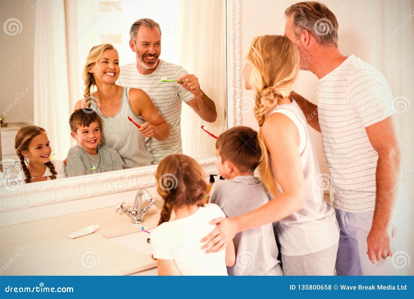 Parents et enfants brossant des dents dans la salle de bains