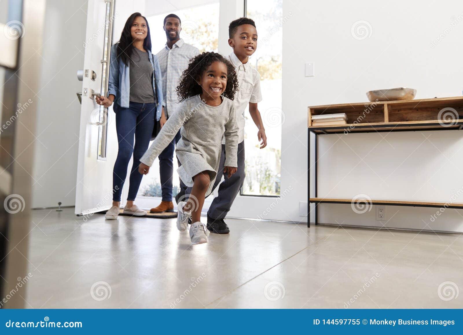 Parents et enfants renvoyant l ouverture à la maison Front Door And Running Inside