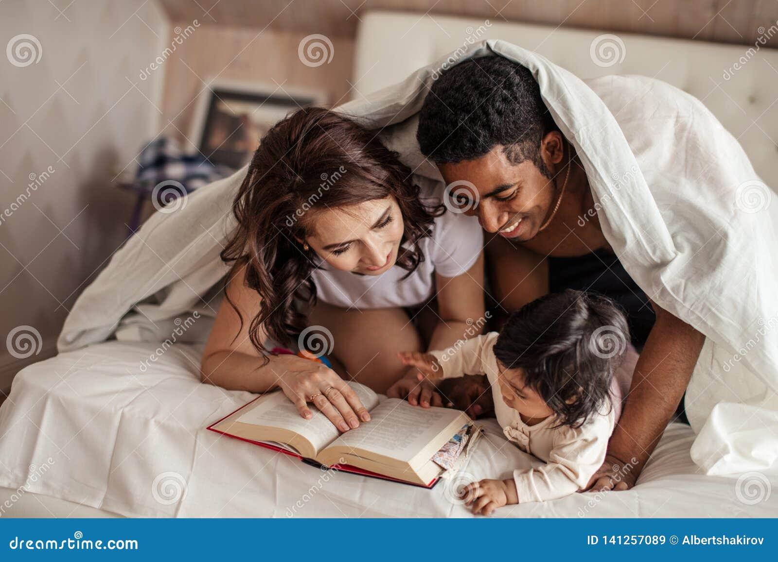 Parents gais lisant les queues féeriques à un bébé avant le sommeil de nuit