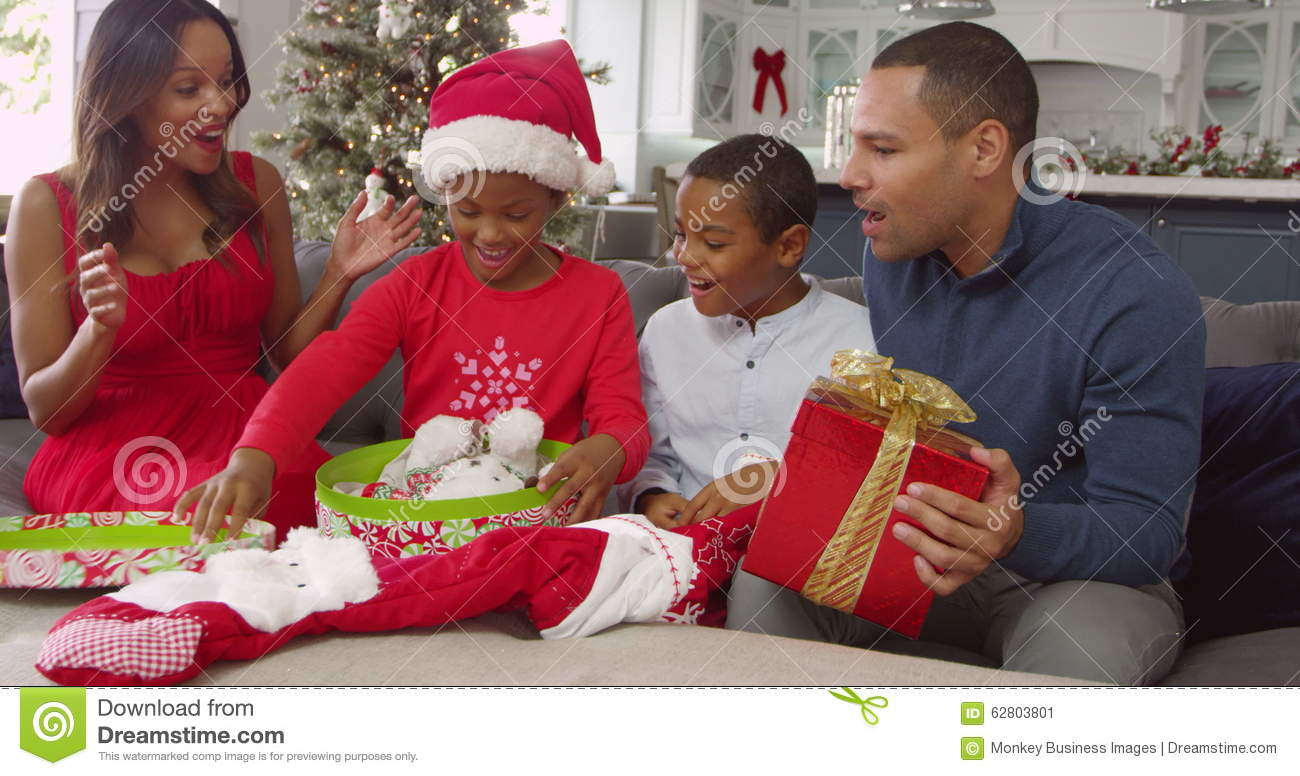 parents giving children christmas gifts at home girl opens box and takes out a cuddly toy reindeer stock video video of female lounge 62803801