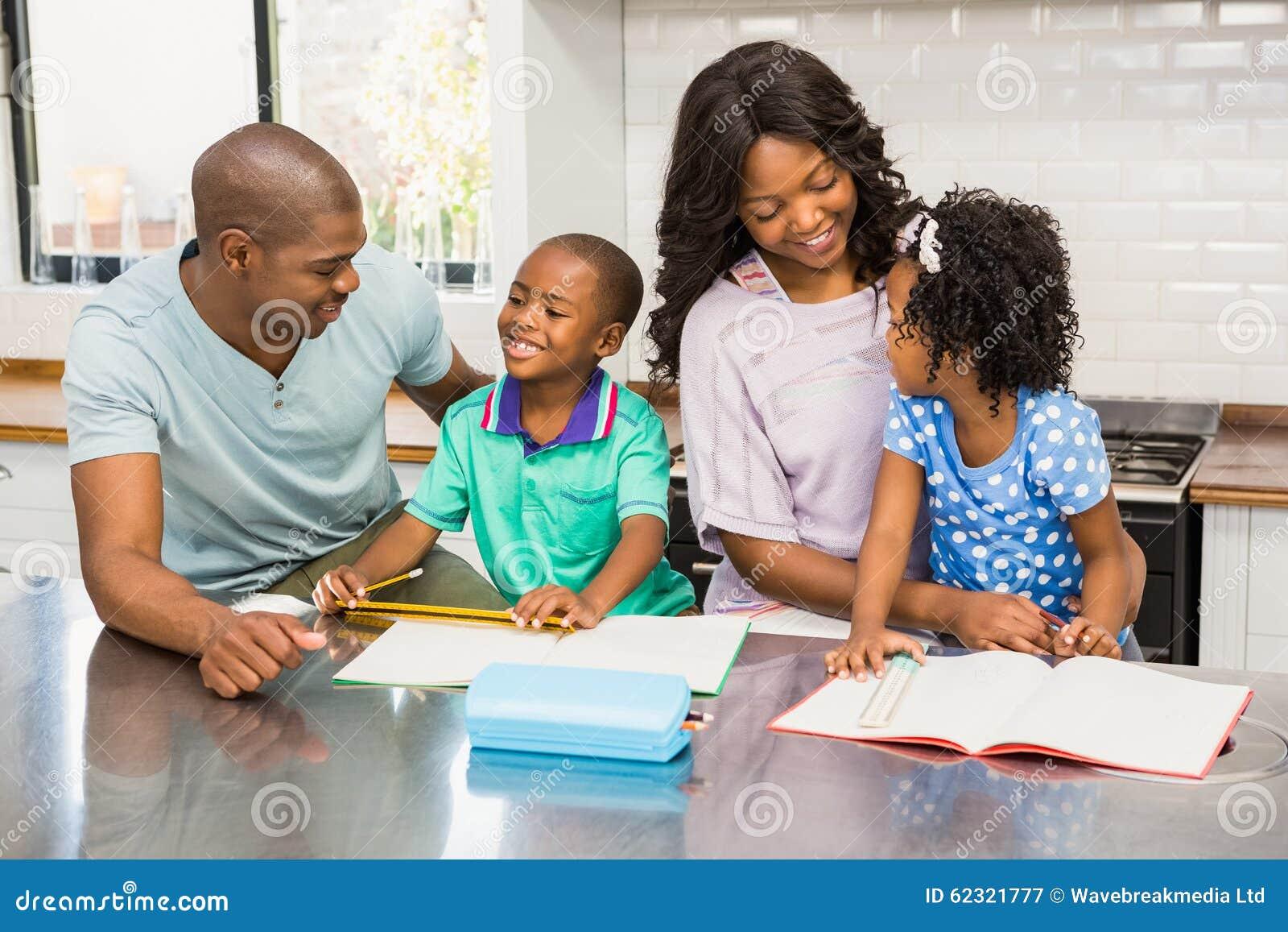 parents helping children doing homework stock photo