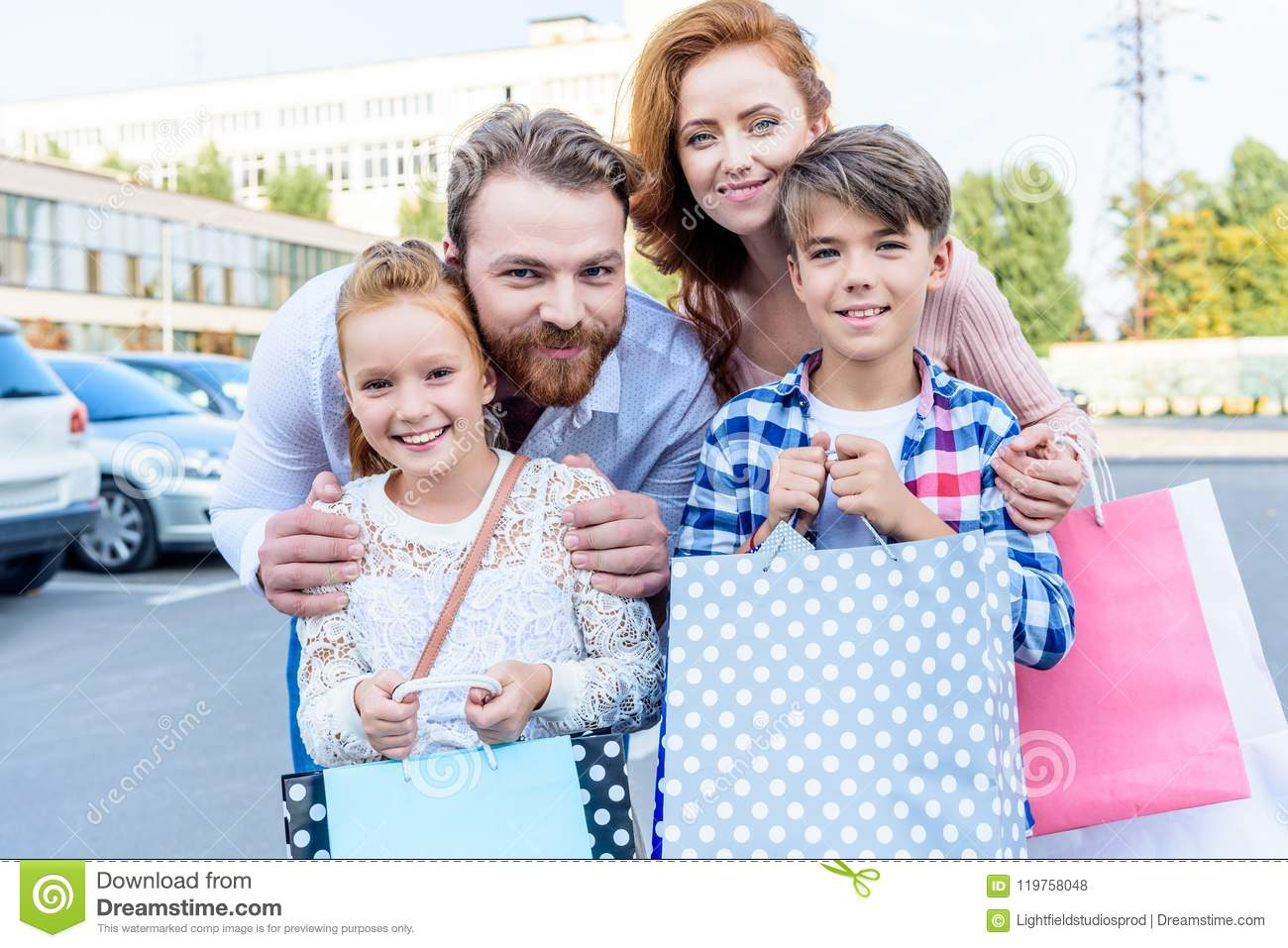 parents hugging children with shopping bags standing on street