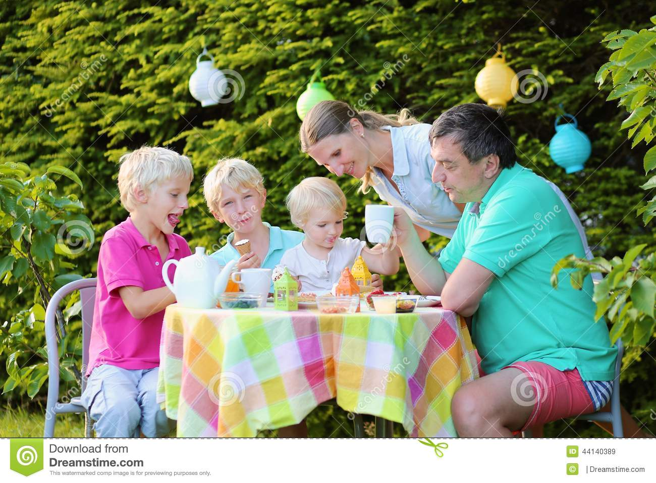 Parents With Kids Having Lunch Outdoors Stock Photo