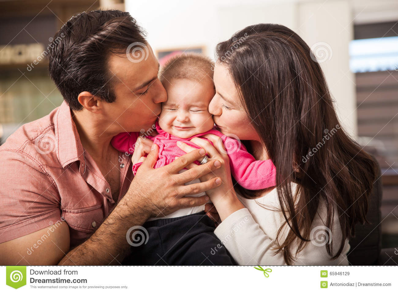 41d98aeb0 Cute baby girl being kissed by both their parents at the same time