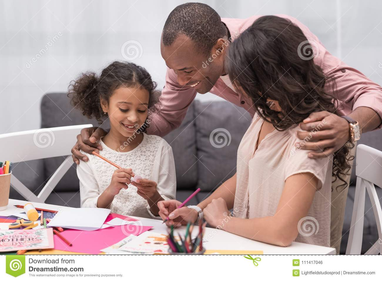 Parents looking how daughter drawing part for greeting card stock royalty free stock photo kristyandbryce Images