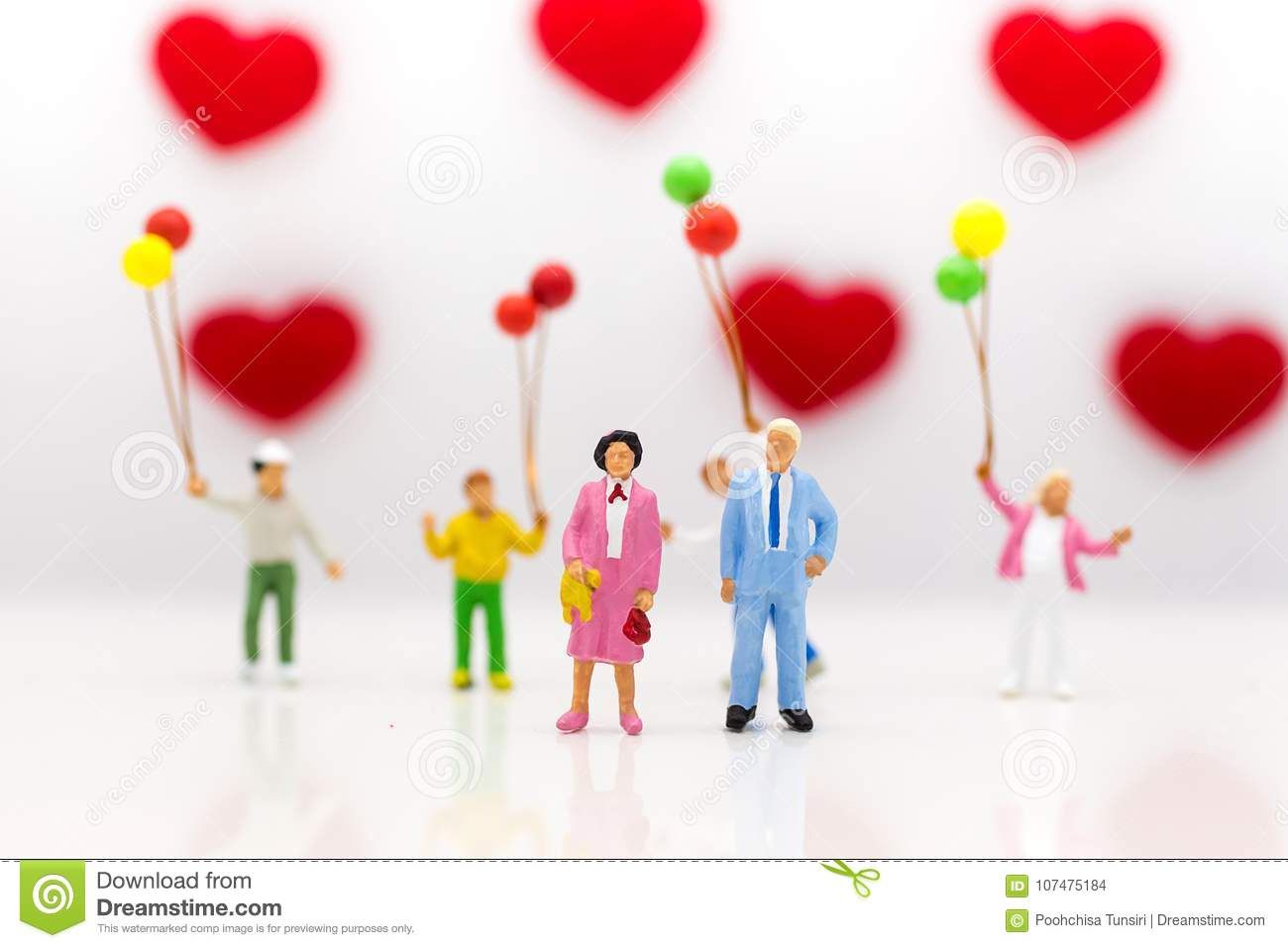 Parents love each other happily, with children playing balloons are behind, used as a wedding anniversary concept