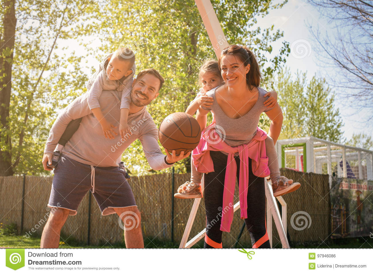Parents playing with their children in the park with basket ball