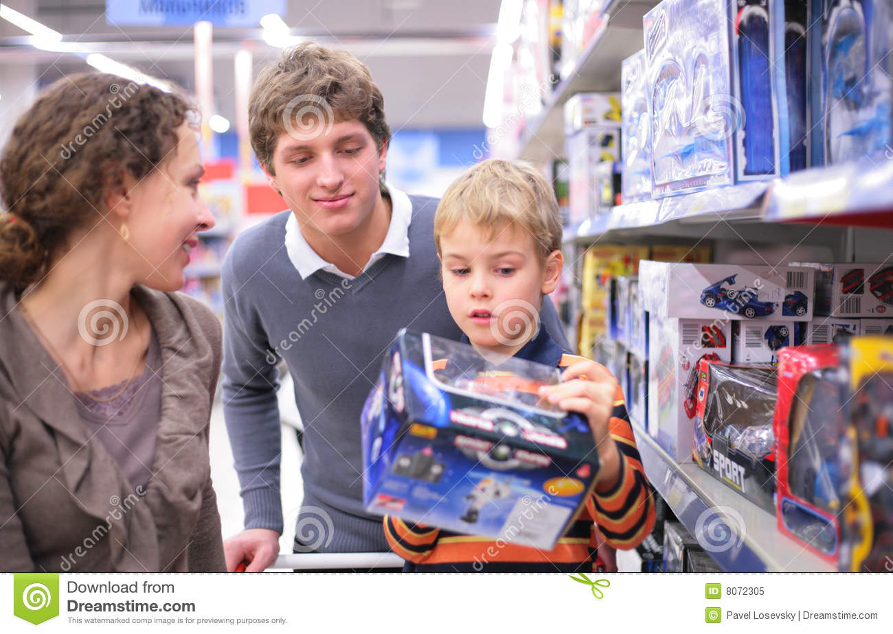 Toys For Parents : Parents with son toy in shop stock image of