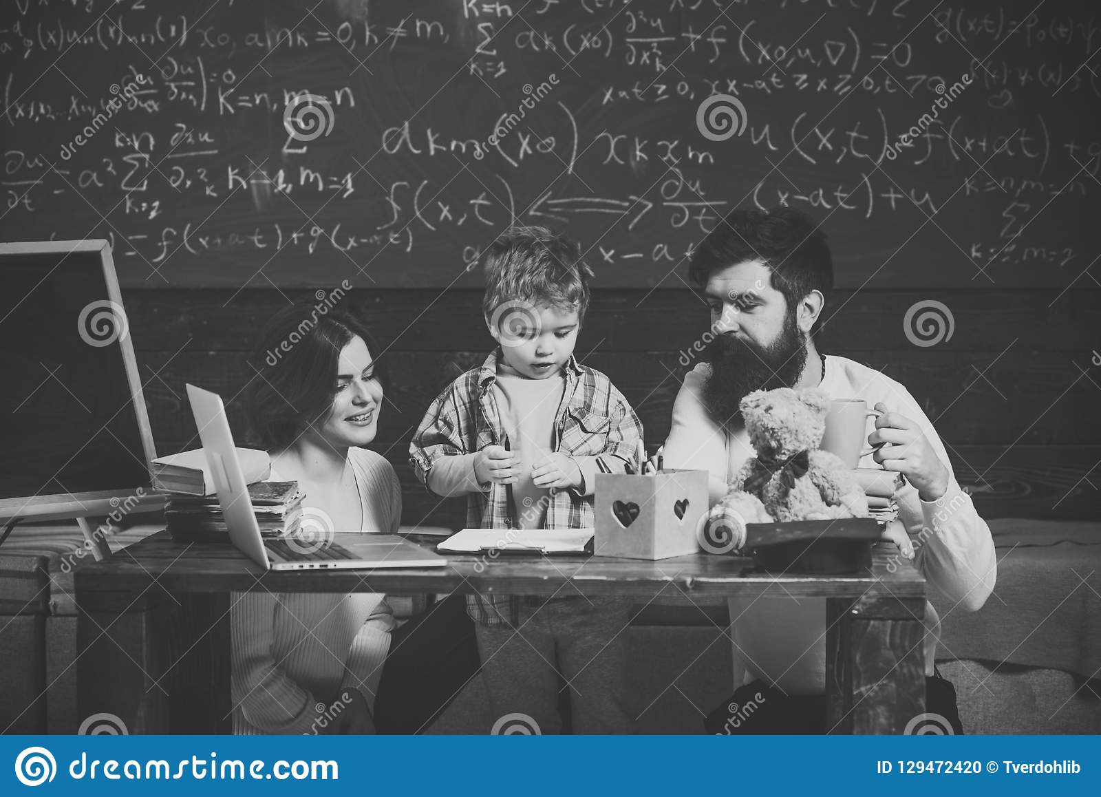 Parents teaches son, chalkboard on background. Boy listening to mom and dad with attention. Family cares about education