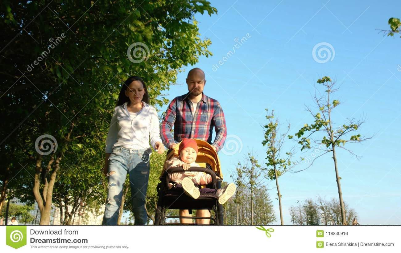 Parents walking with a child in the park. Happy family: Mom and Dad rolled child in pram in nature at sunset