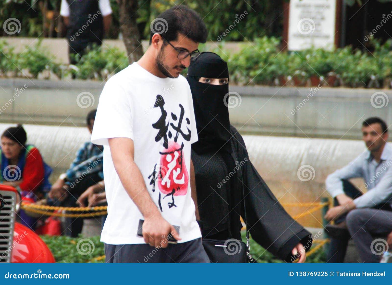 Pares árabes: um homem novo com vidros e uma barba está andando com uma mulher vestida em um burka preto