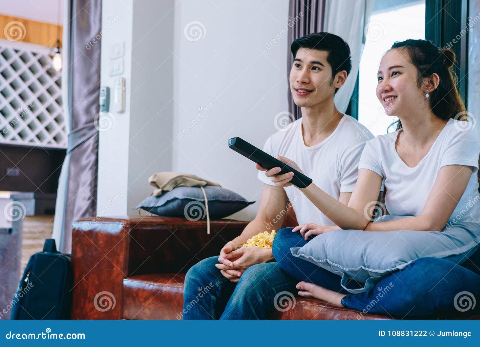 Pares adolescentes asiáticos que ven la TV junto feliz