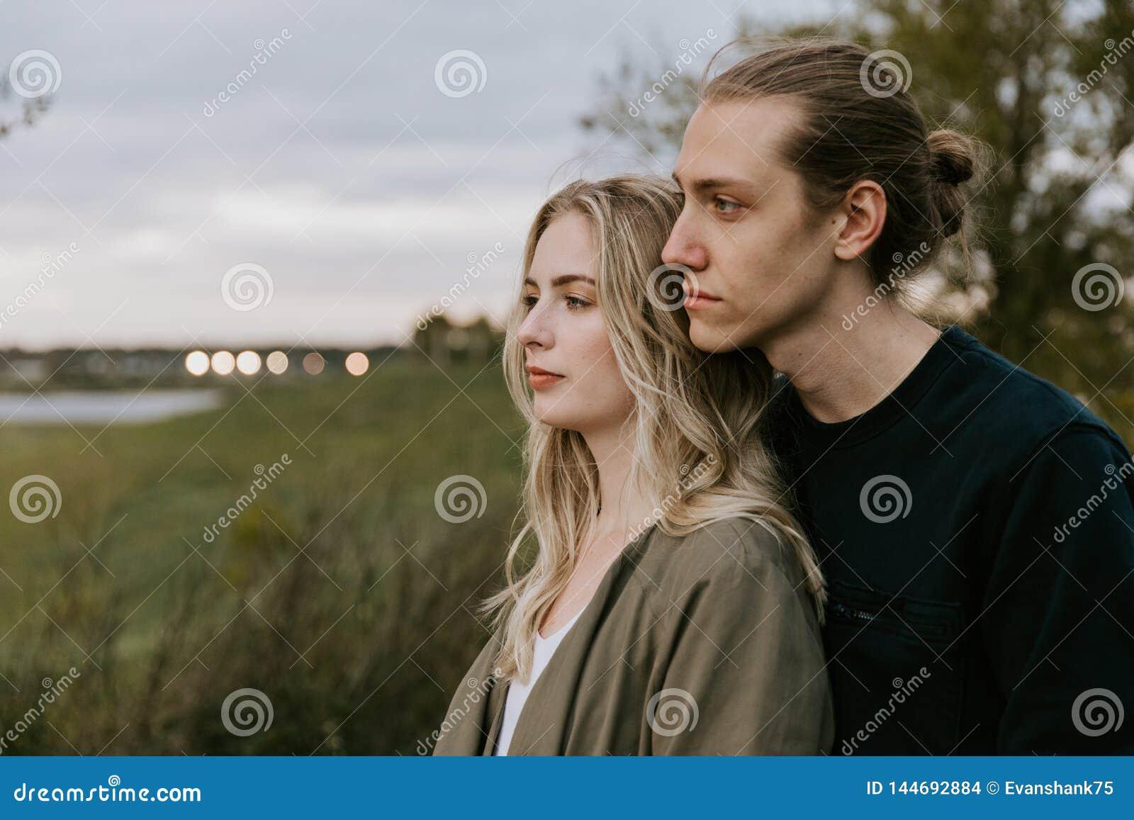 Pares adultos novos românticos e amando no parque que olha a natureza e o horizonte para imagens do retrato
