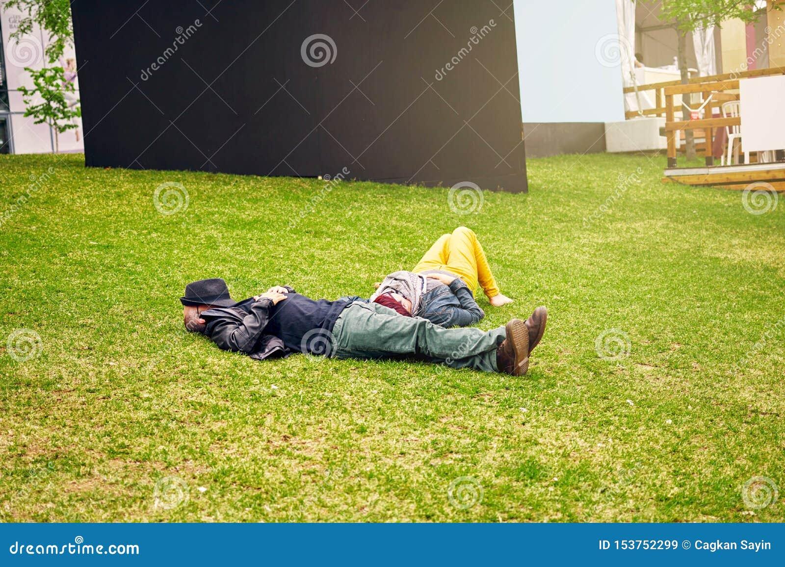 Pares adultos que mienten en el campo de hierba y que toman una siesta La cara del hombre se cubre con su sombrero editorial