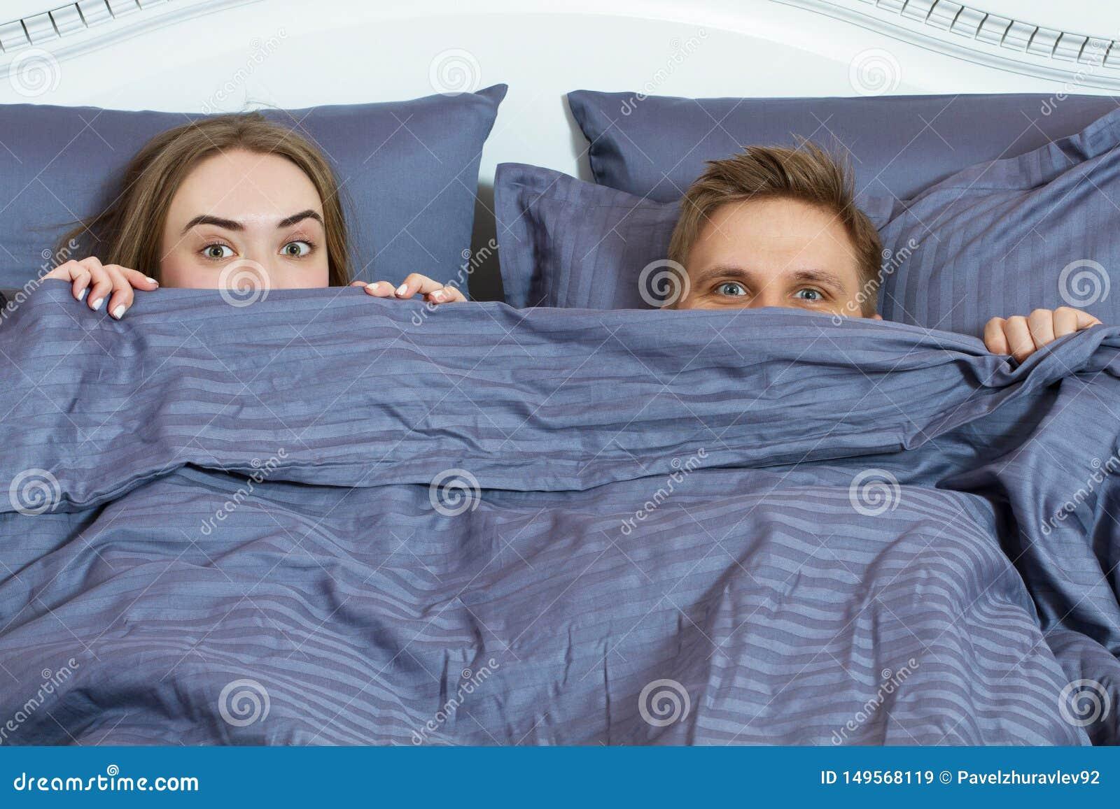 Pares adultos que ocultan debajo de la manta en cama Pares en dormitorio por la ma?ana