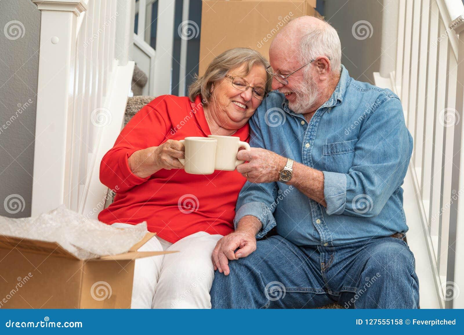 Pares adultos superiores doces em escadas com as canecas de café