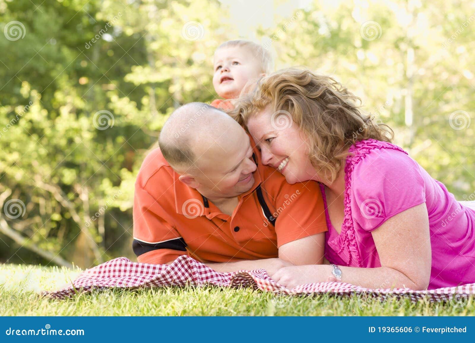 Pares afectuosos com o filho no parque