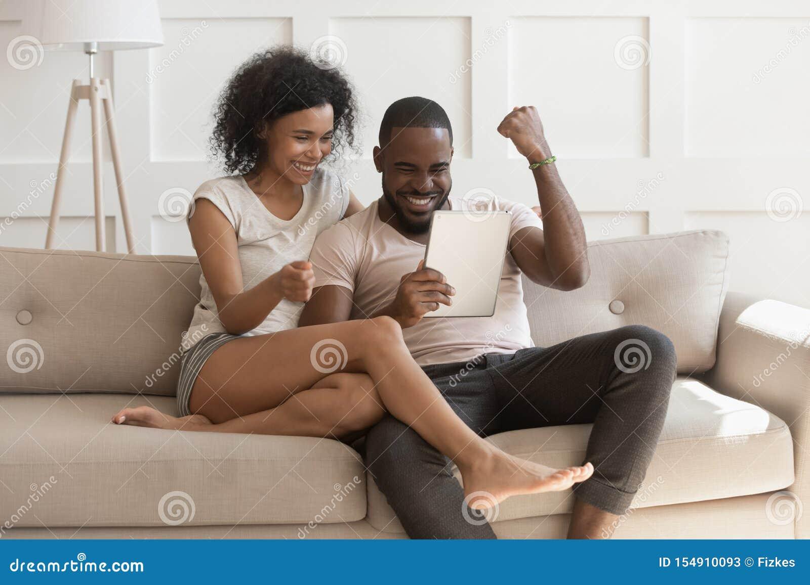 Pares africanos felices emocionados que miran a ganadores digitales de la sensación de la tableta