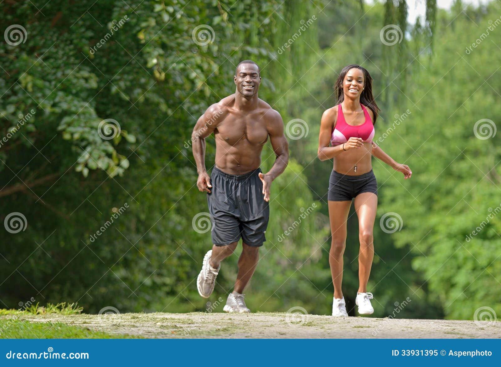Pares afro-americanos atléticos e aptos - movimentando-se em um parque