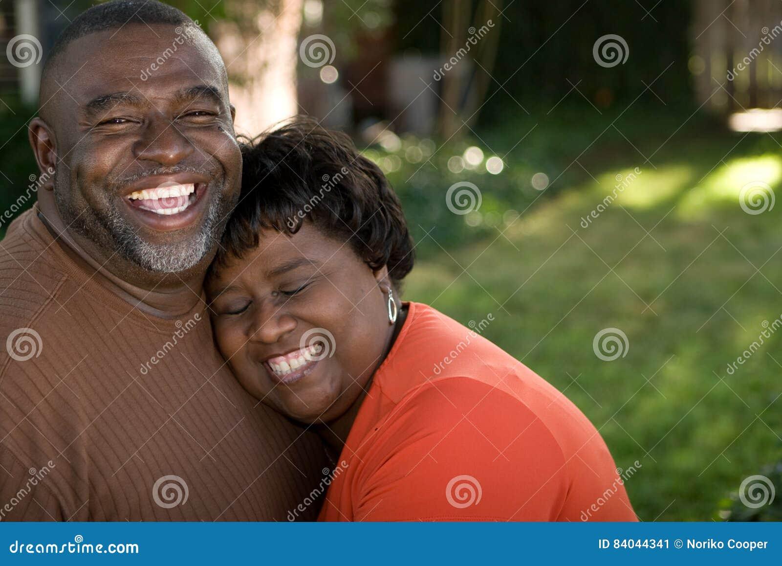 Pares afro-americanos maduros que riem e que abraçam