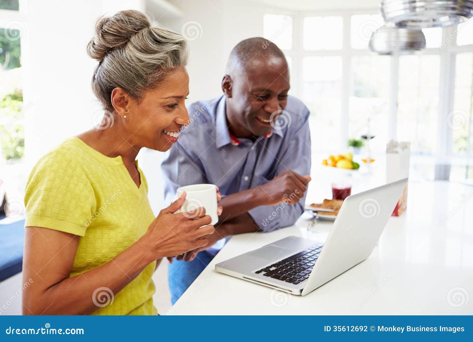 Pares afro-americanos maduros usando o portátil em Bre