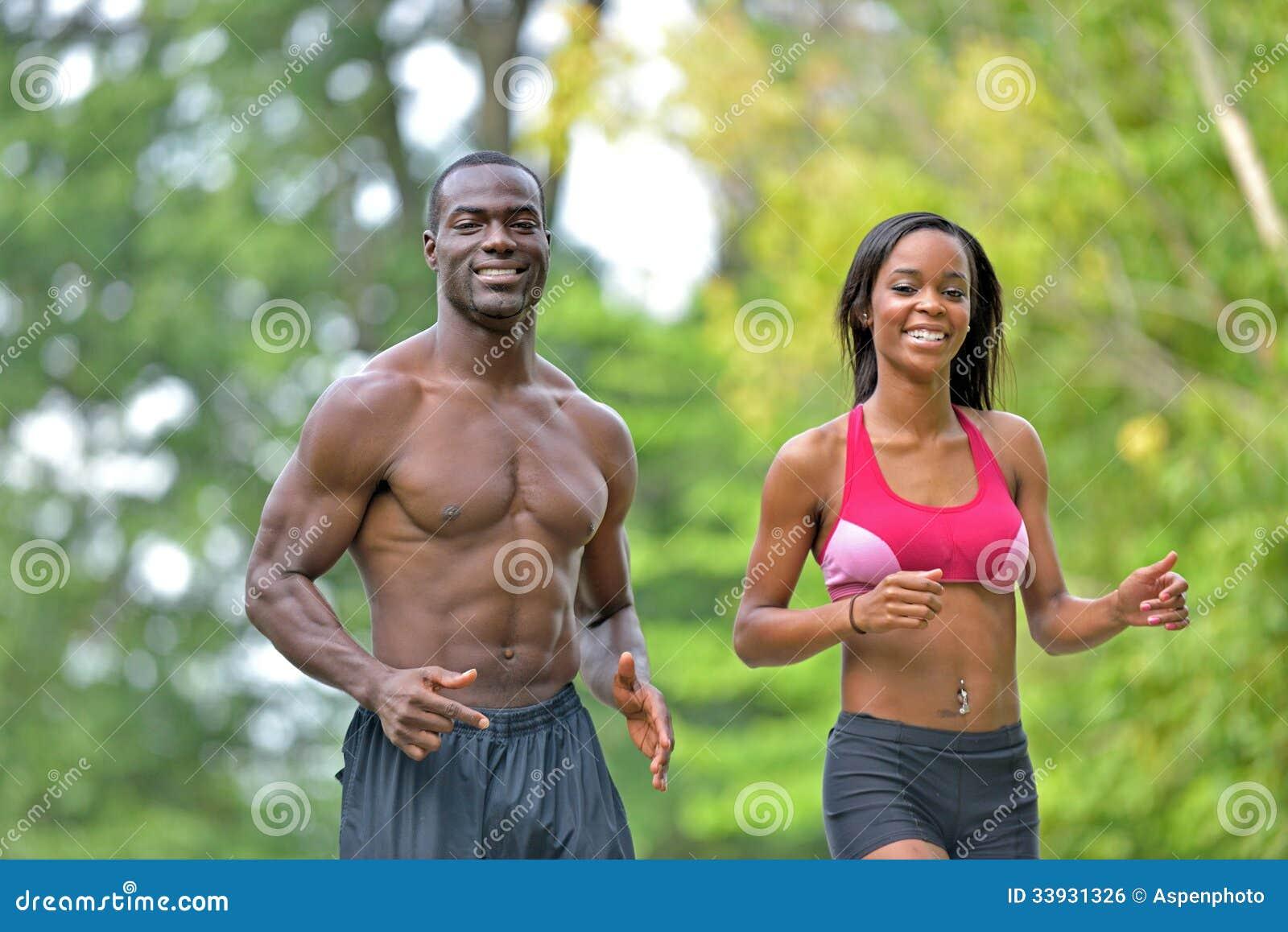 Pares afroamericanos atléticos y aptos - activando en un parque
