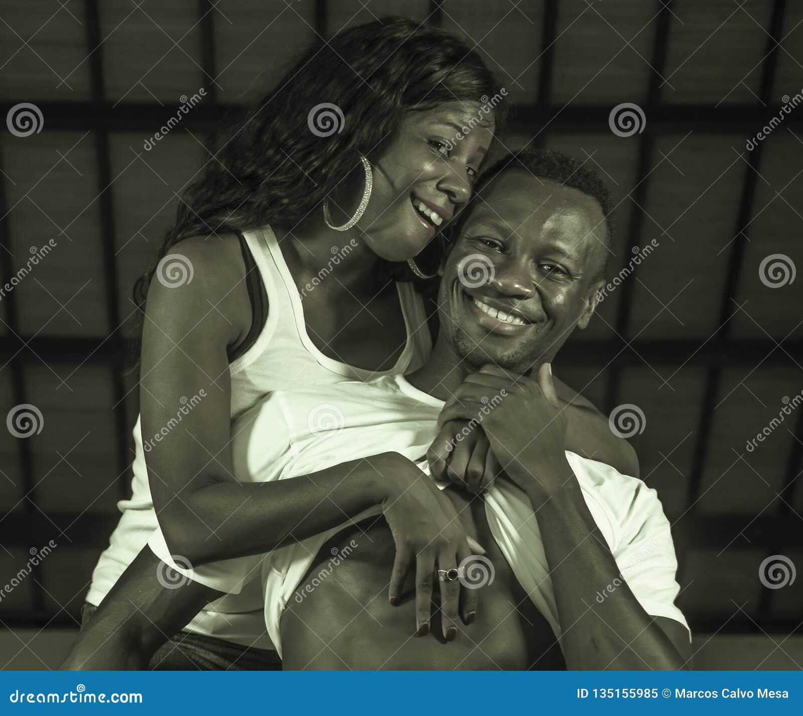 Pares afroamericanos negros felices y atractivos jovenes la demostración del hombre seis abdómenes del paquete y el orgulloso jug