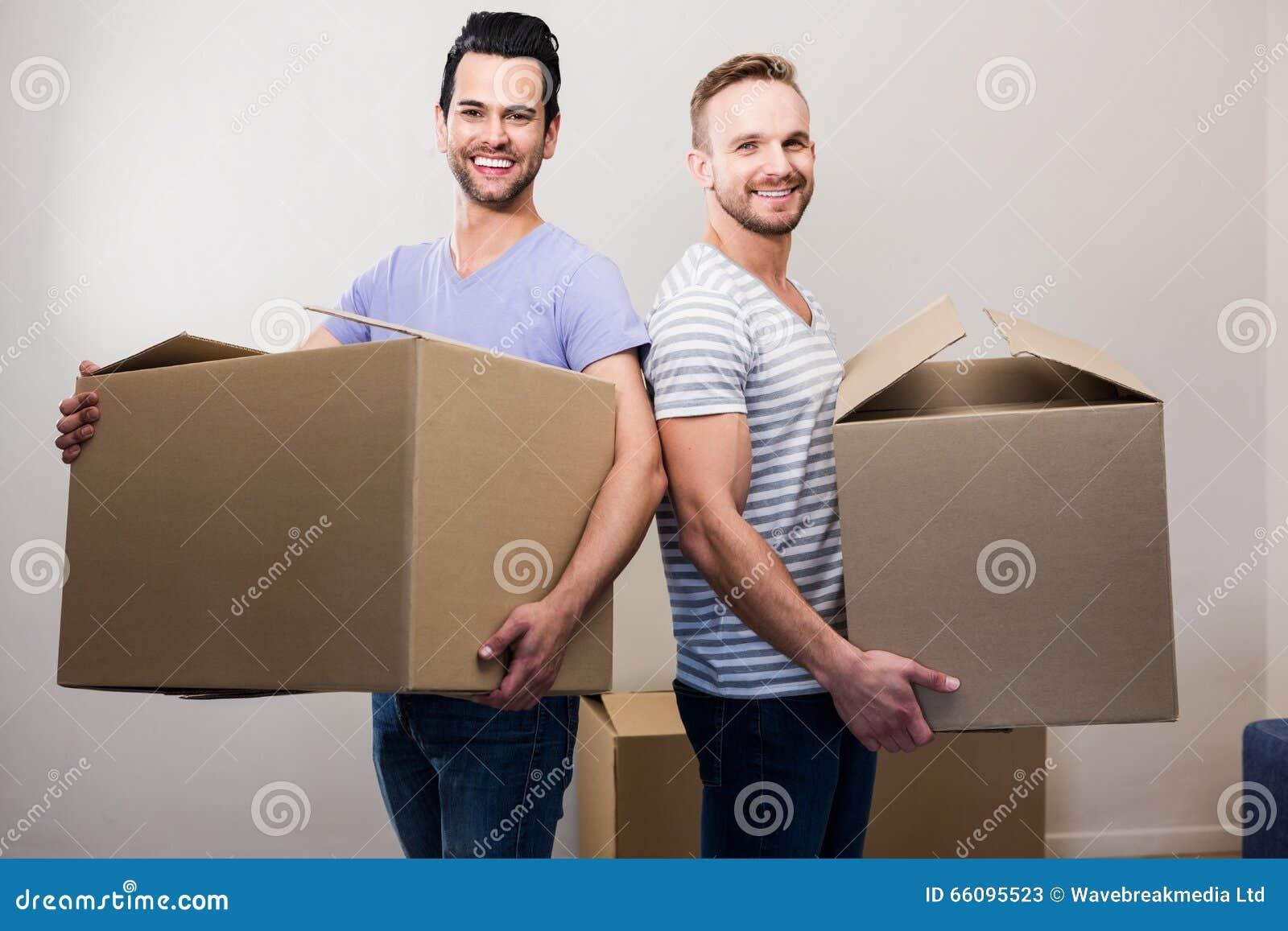 Pares alegres felizes que guardam caixas