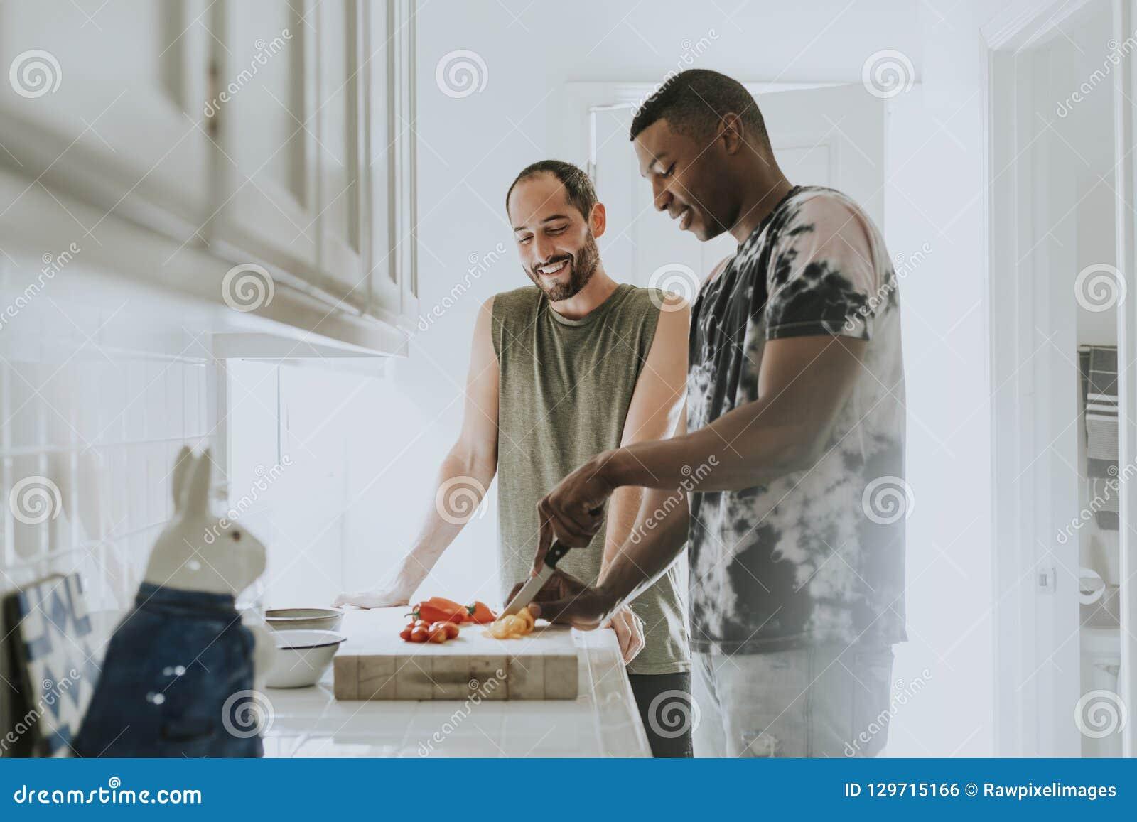 Pares alegres que cozinham na manhã