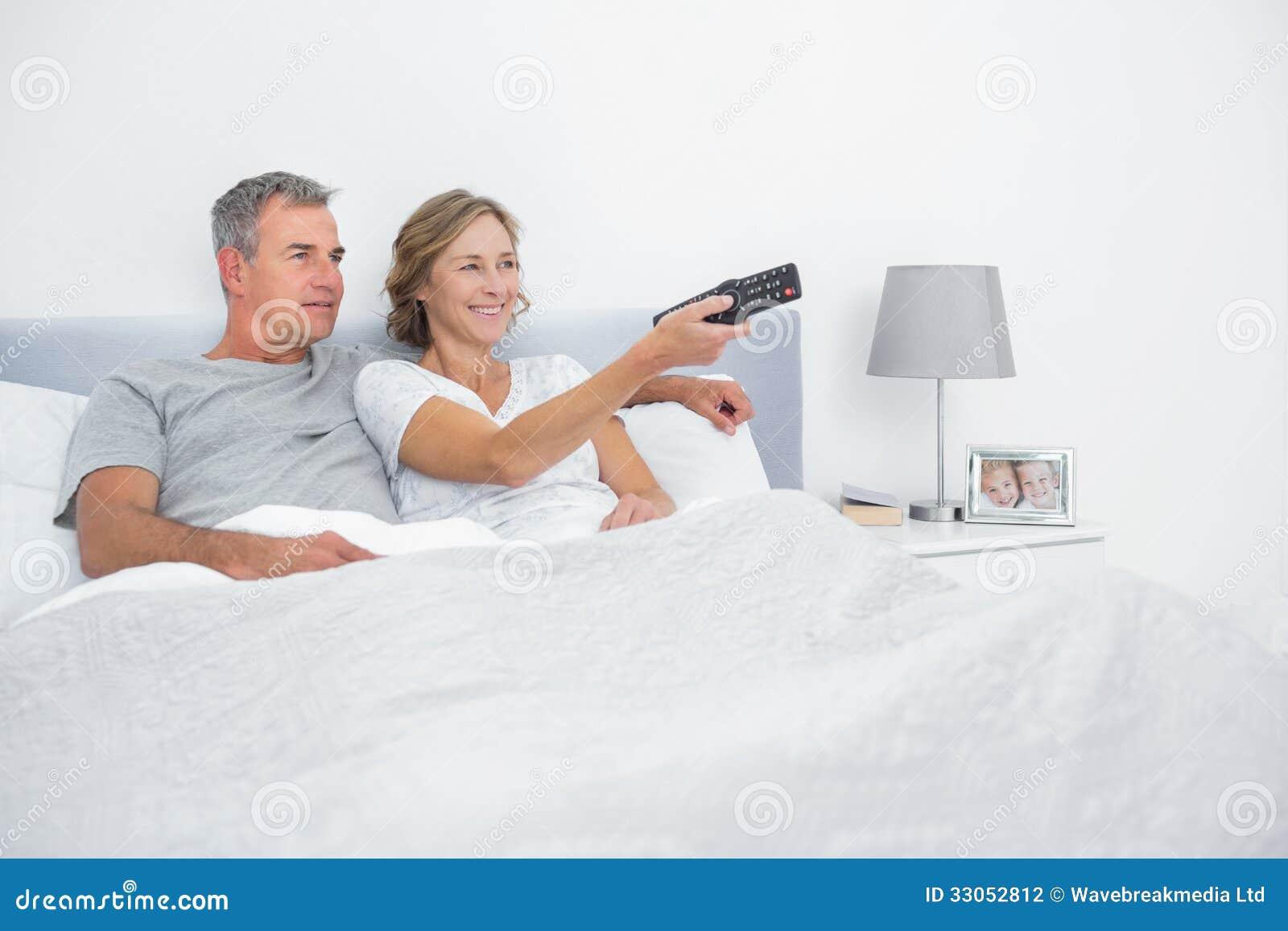 Pares alegres que ven la TV en cama
