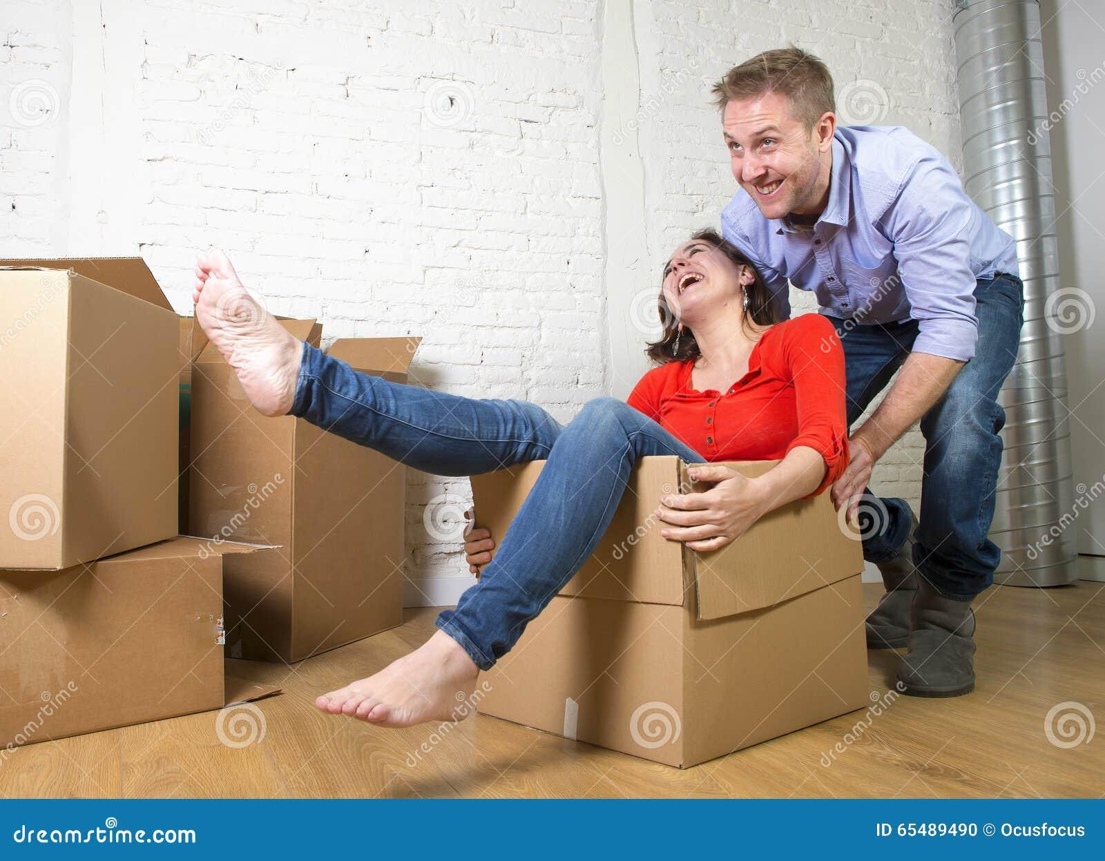 Pares americanos felices que desempaquetan la mudanza en la nueva casa que juega con las cajas de cartón desempaquetadas