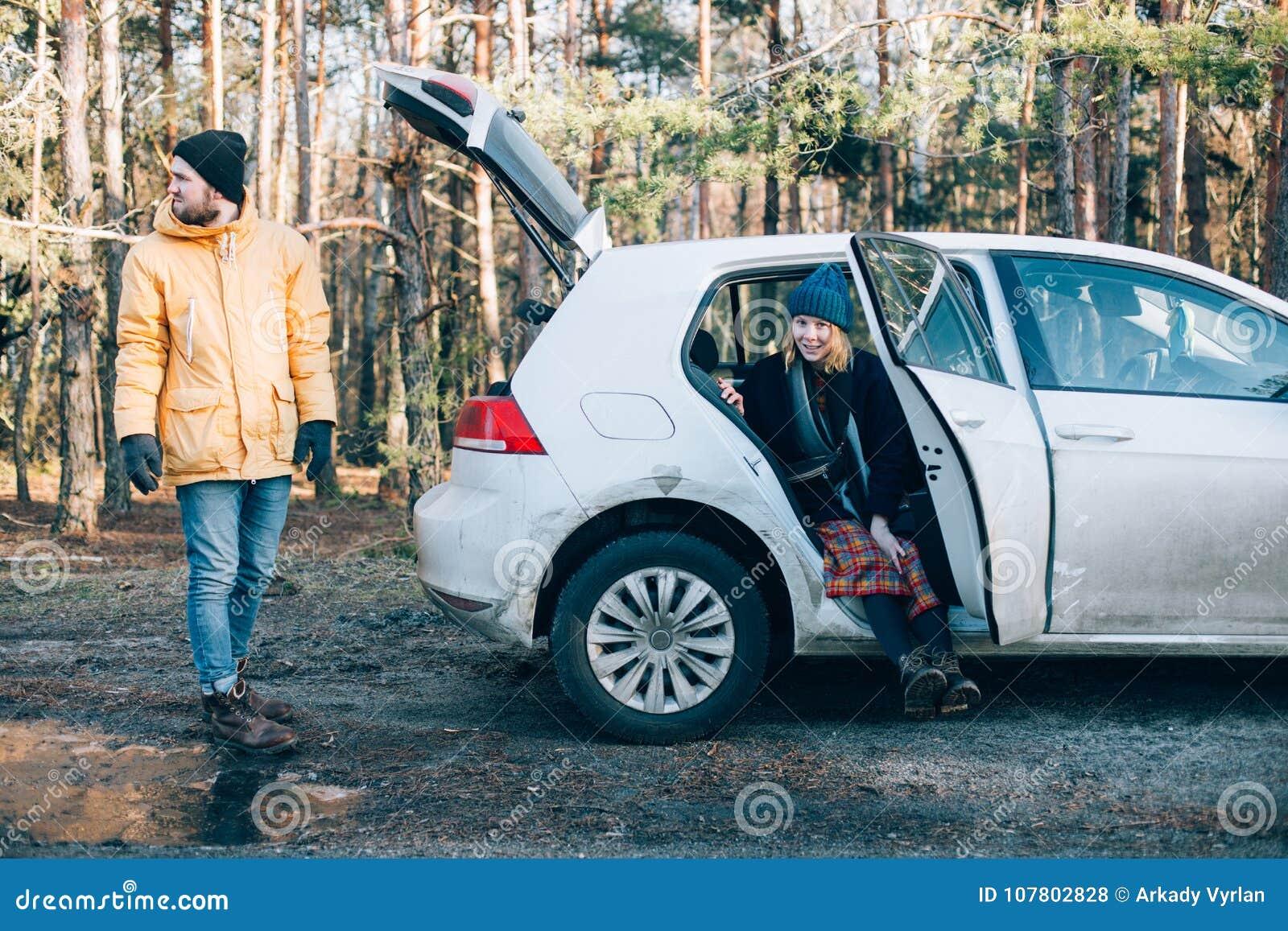 Pares ao lado do carro híbrido pequeno na floresta