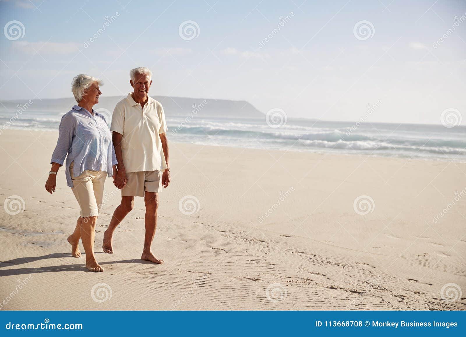 Pares aposentados sênior que andam ao longo da praia em conjunto junto